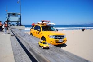 Little Captiva posing in front of lifeguard car & tower, Venice Beach, California