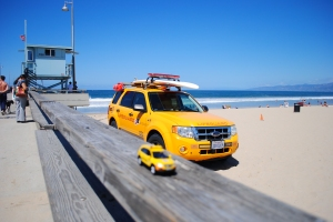 Little Captiva posing in front of lifeguard car & tower, Venice Beach, California